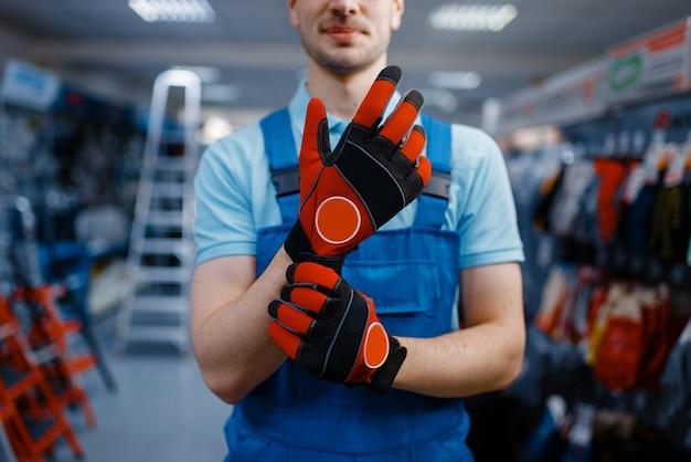Trabalhador do sexo masculino com as mãos em luvas de proteção, loja de ferramentas