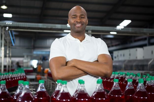 Trabalhador do sexo masculino confiante operando máquina em fábrica de bebidas frias
