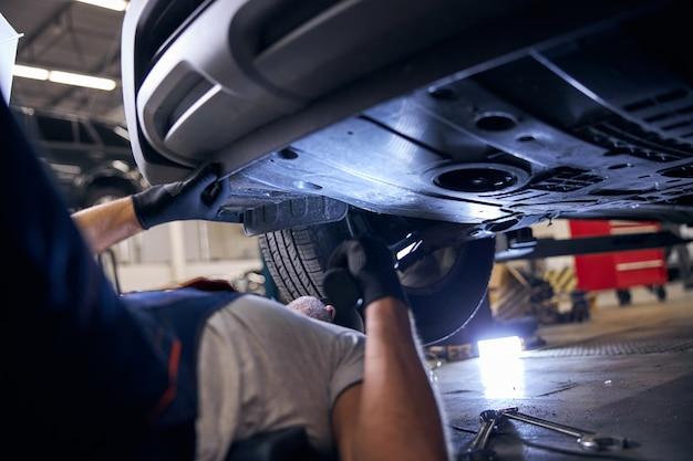 Trabalhador do sexo masculino consertando carro em posto de gasolina