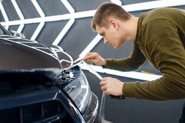 Trabalhador do sexo masculino corta película de proteção transparente no capô do carro. instalação de revestimento que protege a pintura do automóvel de arranhões. novo veículo na garagem, autotuning