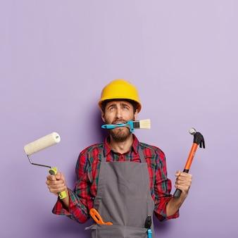 Trabalhador do sexo masculino de reparos domésticos ocupado com a reforma da casa, guarda equipamentos de construção