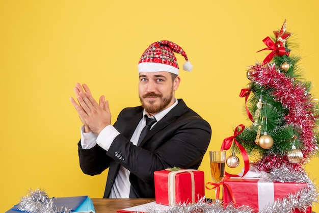 Trabalhador do sexo masculino de vista frontal sentado atrás de seu local de trabalho batendo palmas no amarelo