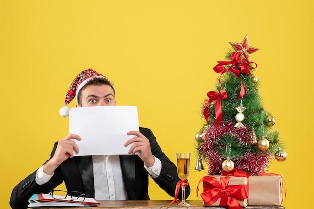 Trabalhador do sexo masculino de vista frontal sentado atrás de seu local de trabalho segurando documentos com uma cara de surpresa