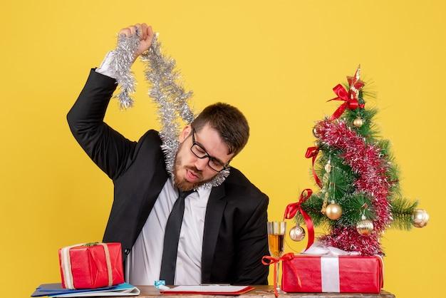 Trabalhador do sexo masculino de vista frontal sentado atrás de sua mesa em amarelo