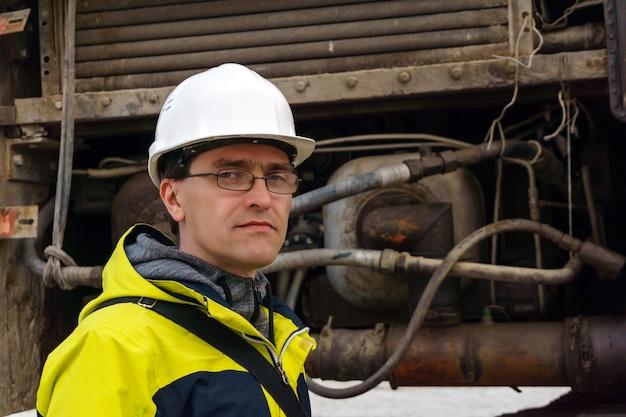 Trabalhador do sexo masculino em um capacete no contexto das unidades hidráulicas de alguma máquina de construção