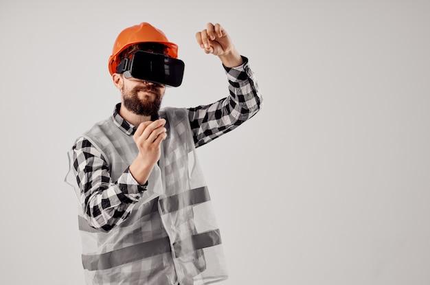 Trabalhador do sexo masculino em um fundo isolado profissional de tecnologia de capacete laranja