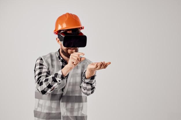 Trabalhador do sexo masculino em uma tecnologia de capacete laranja luz de fundo profissional