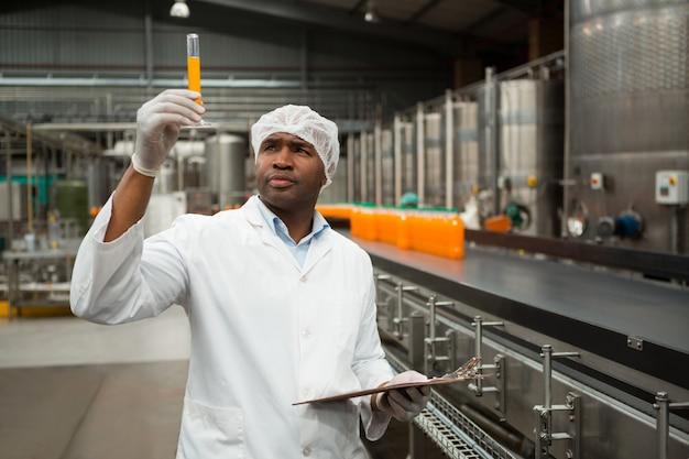 Trabalhador do sexo masculino examinando suco na fábrica