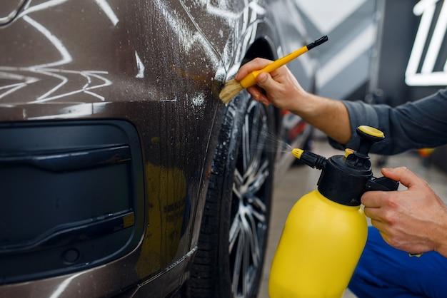 Trabalhador do sexo masculino limpa a superfície do carro com spray e pincel, preparação antes da aplicação da película protetora, detalhamento. instalação de revestimento que protege a pintura do automóvel de arranhões