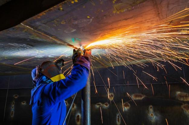 Trabalhador do sexo masculino moendo na placa de aço com flash de faíscas perto de usar luvas de proteção de óleo dentro de espaços confinados.