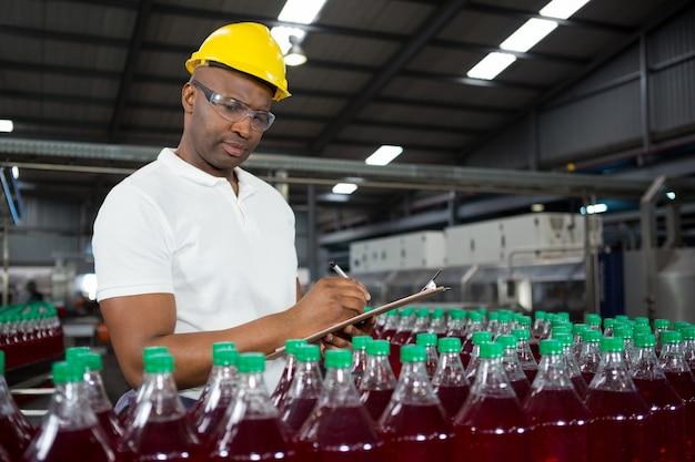Trabalhador do sexo masculino observando sobre produtos no armazém