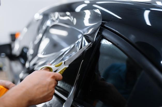 Trabalhador do sexo masculino segura folha de filme, instalação de tingimento de carro, serviço de ajuste. mecânico aplicando tinta de vinil na janela do veículo na garagem, vidro escurecido do automóvel