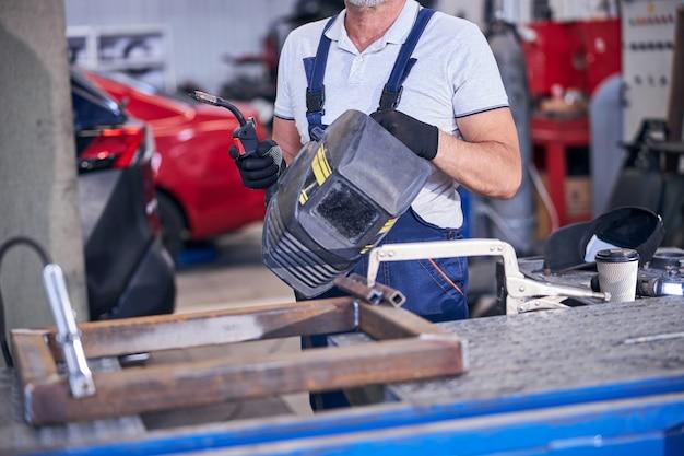 Trabalhador do sexo masculino segurando tocha de soldagem e capacete de soldagem