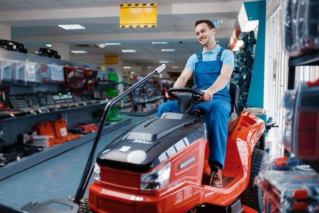 Trabalhador do sexo masculino sentado no cortador de grama na loja de ferramentas