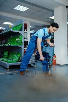 Trabalhador do sexo masculino testando um grande perfurador elétrico no chão de uma loja de ferramentas, humor ou piada