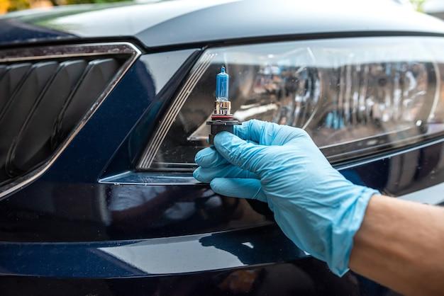 Trabalhador do sexo masculino troca lâmpada no conceito de farol, conserto de automóveis e serviço