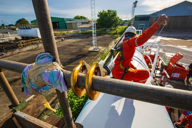 Trabalhador do sexo masculino usando arnês de segurança e solitário de segurança trabalhando em um andaime alto em óleo de telhado de tanque superior aberto