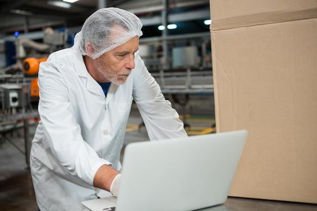 Trabalhador do sexo masculino usando laptop em fábrica de bebidas geladas