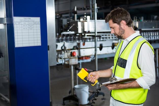 Trabalhador do sexo masculino usando máquinas na fábrica de suco