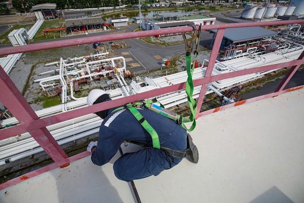 Trabalhador do sexo masculino usando primeiro arnês de segurança e solitário de segurança trabalhando em lugar de corrimão alto em óleo de telhado de tanque superior aberto