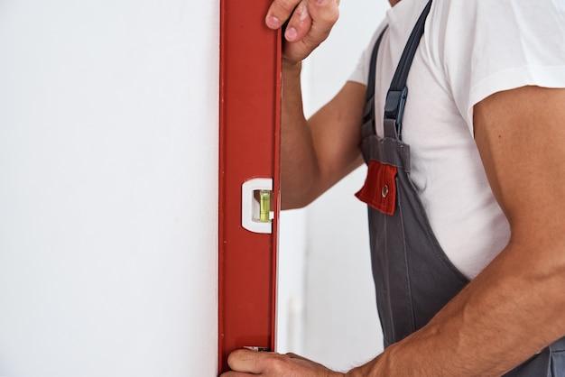 Trabalhador do sexo masculino verificando o nível da parede com a ferramenta de nível de bolha