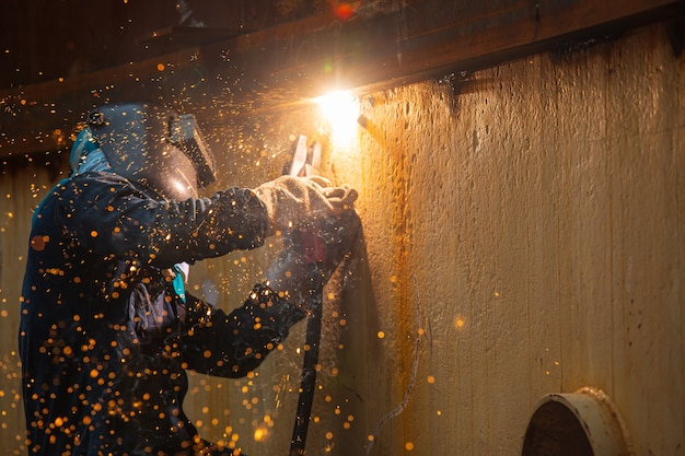 Trabalhador do sexo masculino vestindo roupas de proteção e reparo de soldagem de faísca placa de concha óleo de construção industrial e gás ou tanque de armazenamento dentro de espaços confinados.