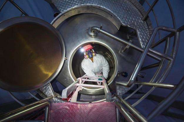 Trabalhador do sexo masculino vista de cima subindo as escadas para a área de produtos químicos do tanque segurança em espaço confinado