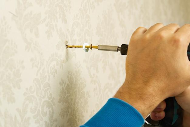 Trabalhador doméstico enfia o parafuso na parede de concreto usando uma chave de fenda elétrica.