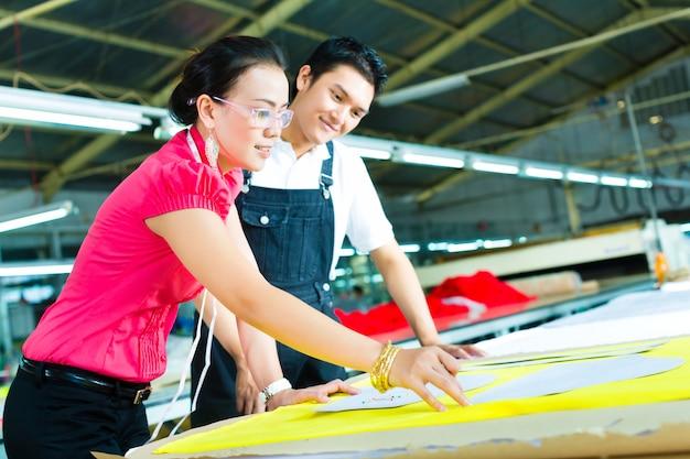 Trabalhador e costureira em uma fábrica