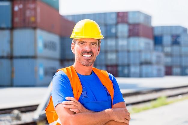 Trabalhador e linha de contentores no porto