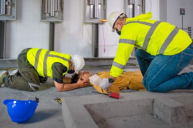 Trabalhador elétrico sofreu um acidente por choque elétrico inconsciente. rcp da equipe de segurança para primeiros socorros eletricista perde em acidente por choque elétrico no local de trabalho. acidente na sala de controle da fábrica.