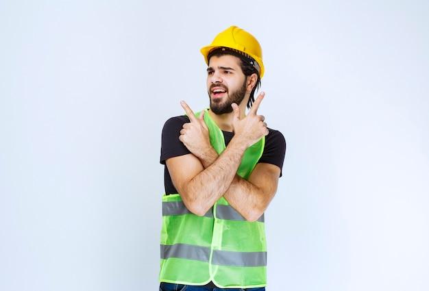 Trabalhador em capacete amarelo e jaqueta verde apontando para cima.