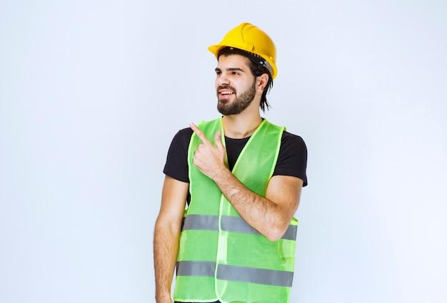 Trabalhador em capacete amarelo mostrando o lado esquerdo.