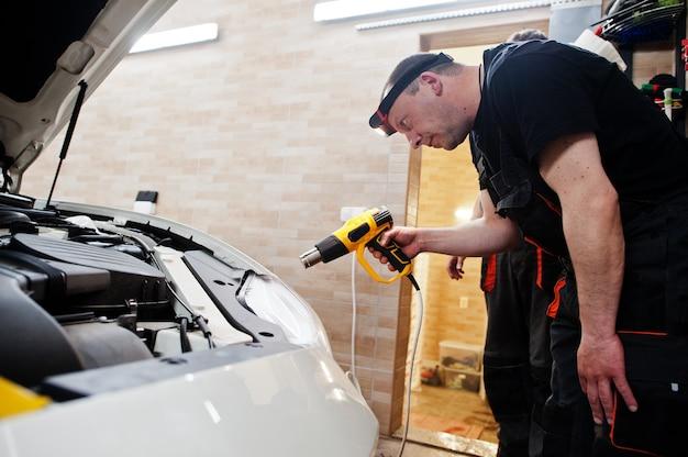 Trabalhador em detalhamento de garagem segurar soprador de ar quente em carro de luxo branco.