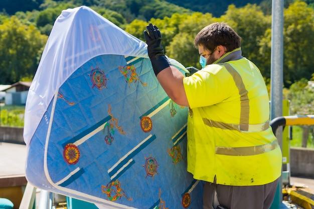 Trabalhador em fábrica de reciclagem ou ponto limpo e lixo com máscara facial e com proteções de segurança, novo normal. limpeza do operador e ordenação da instalação