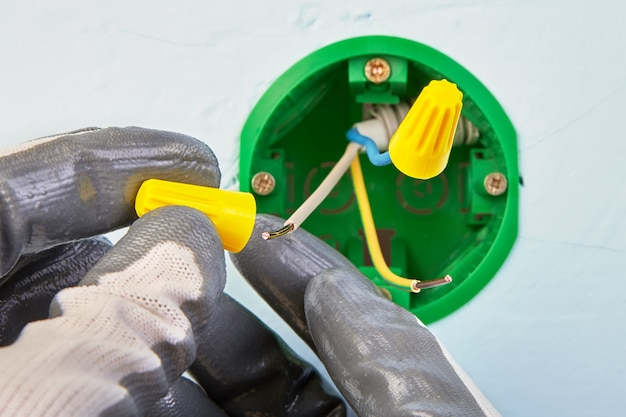Trabalhador em luvas de proteção está colocando condutores elétricos em fios em uma caixa elétrica redonda para interruptor de luz de parede.