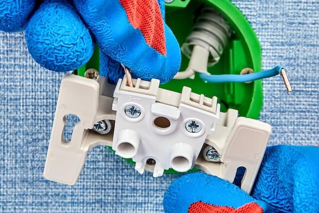 Trabalhador em luvas de proteção está conectando duas partes da caixa de tomada redonda de padrão europeu, manutenção elétrica.