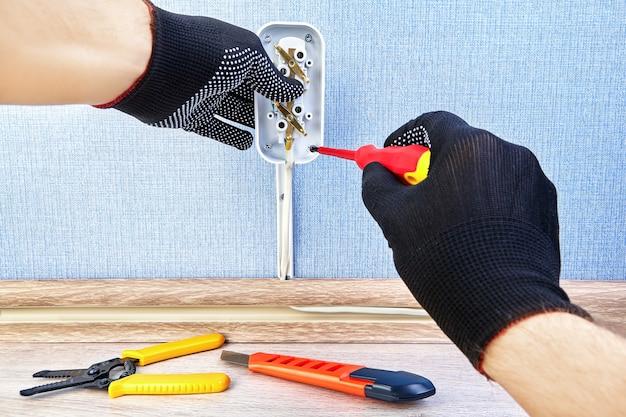 Trabalhador em luvas de proteção está torcendo o parafuso na nova tomada elétrica com uma chave de fenda.