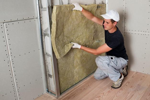 Trabalhador em luvas de proteção, isolando o isolamento de lã de rocha em moldura de madeira para futuras paredes da casa para barreira fria. confortável casa quente, economia, construção e conceito de renovação