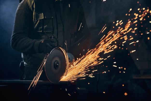 Trabalhador em luvas de proteção polindo metal com faíscas