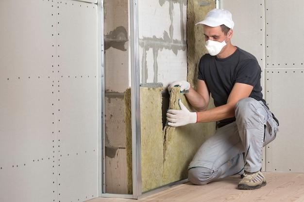 Trabalhador em máscara de proteção respiratória isolante de lã de rocha isolante em madeira