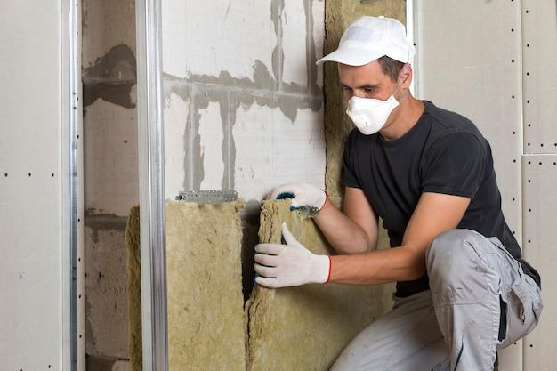 Trabalhador em máscara de respirador máscara isolante isolamento de lã de rocha em moldura de madeira para paredes da casa futura para barreira fria.