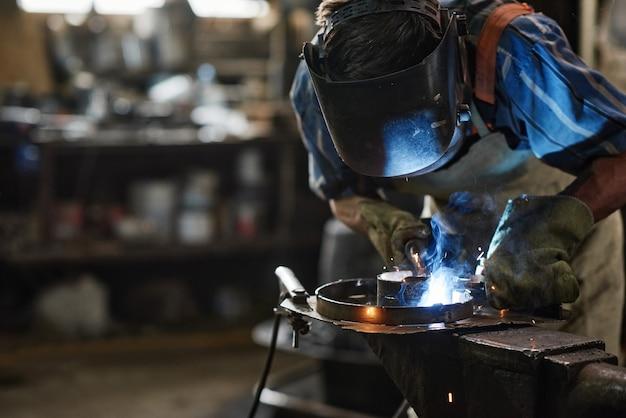 Trabalhador em máscara protetora soldando metal com equipamento especial na oficina