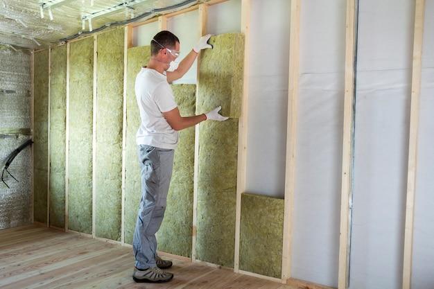 Trabalhador em óculos de proteção e isolamento de lã de rocha isolante respirador em moldura de madeira para paredes da casa futura para barreira fria. confortável casa quente, economia, construção e conceito de renovação