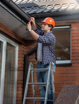 Trabalhador em pé na escada e consertando a calha da casa