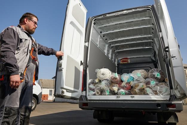 Trabalhador em pé perto de um caminhão cheio de tapetes, conceito de serviço de limpeza