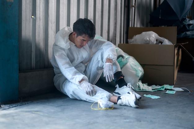 Trabalhador em ppe exausto e experimentado em fábricas de reciclagem de resíduos durante covid-19 e pandemia.