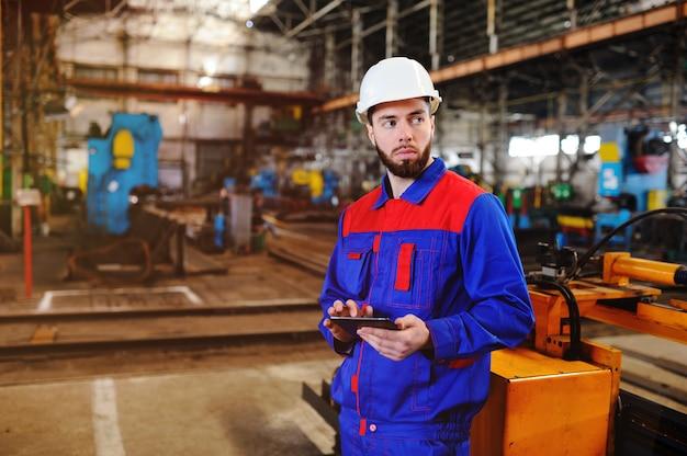 Trabalhador em um capacete com um tablet
