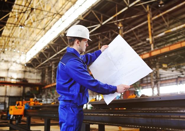 Trabalhador em um capacete de construção com um desenho no fundo de uma planta