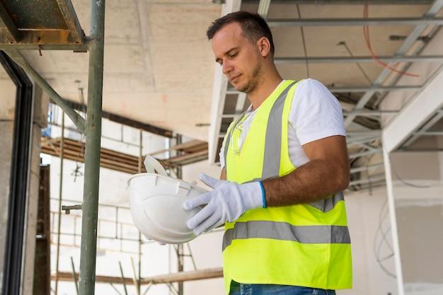 Trabalhador em uma construção segurando um capacete